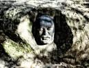 Una de las figuras más oscuras surge de la oscuridad, con un semblante lleno de concentración, parece un espíritu surgido de las entrañas de la tierra